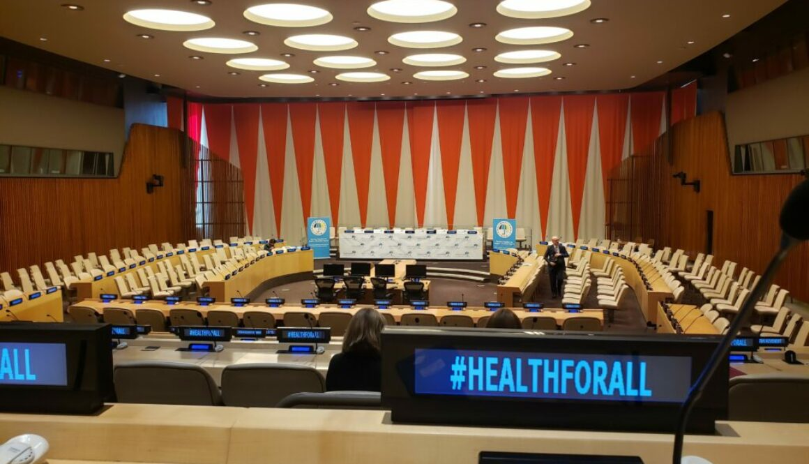Photo of the UN meeting room and the hashtag #HealthForAll on a computer screen