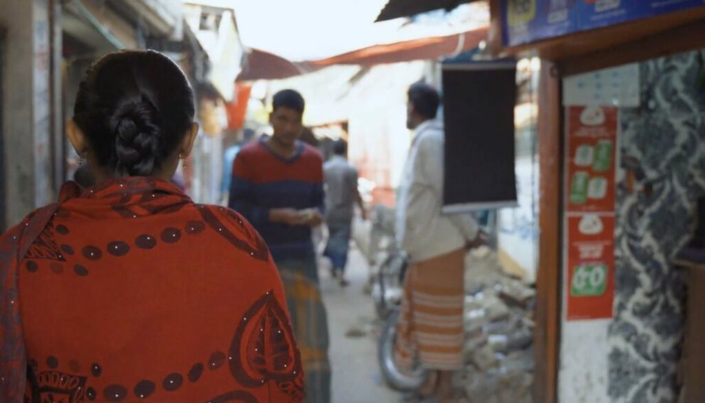 A woman in an orange top with dark, long hair which is tied back is seen from behind. She is in the foreground and in the background you can see she is walking down a narrow alley in an informal settlement. She is walking towards shops and three men in the distance who are walking around.
