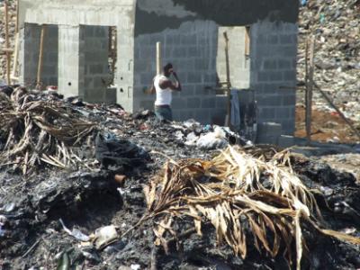 A man walking past a heap of garbage
